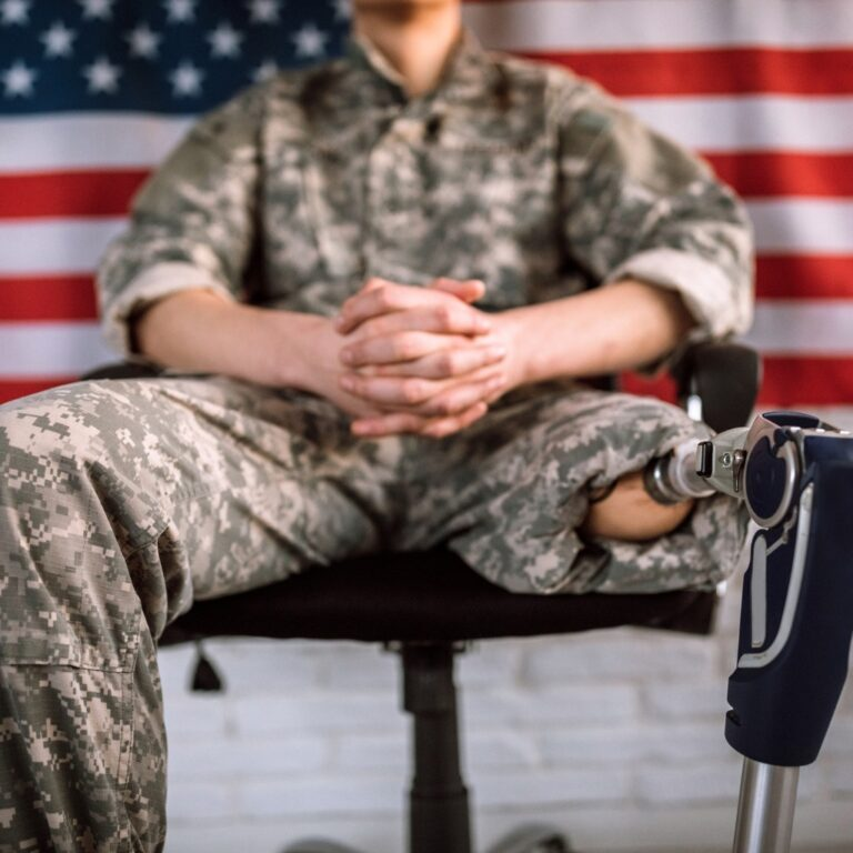 unrecognizable-soldier-with-amputee-leg-sitting-in-chair